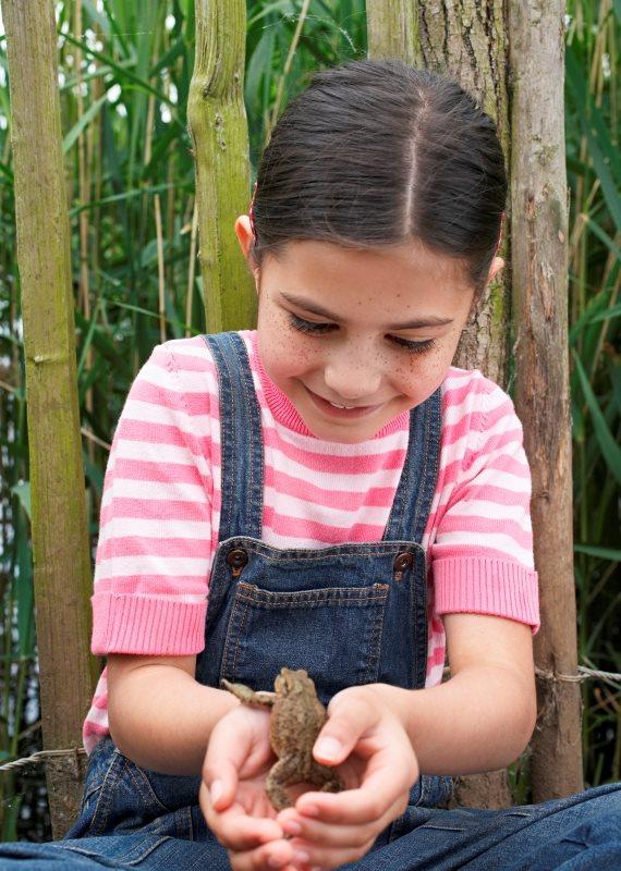 ילדה מחזיקה צפרדע
