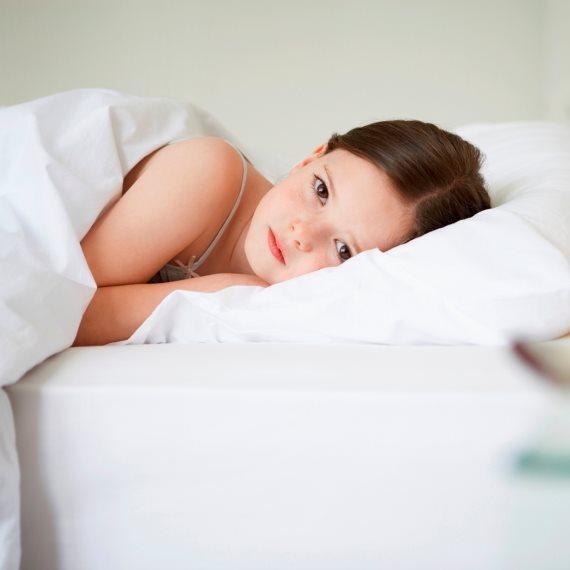 ילדה עצובה במיטה