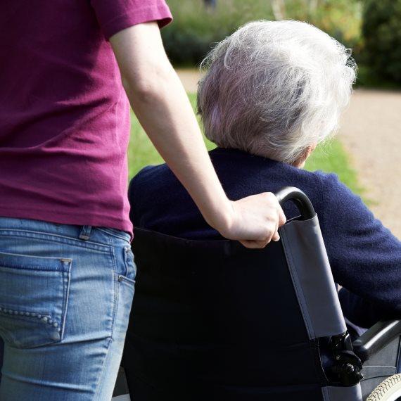מטפלת מטיילת עם קשישה על כיסא גלגלים