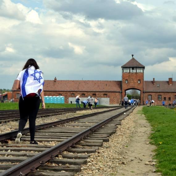 נערה עטופה בדגל ישראל באושוויץ, פולין