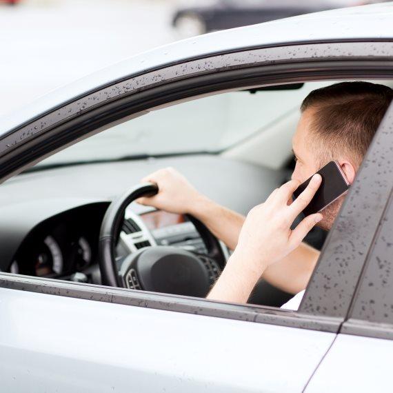איש נוהג ומדבר בטלפון
