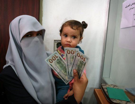 אישה בעזה מקבלת כסף שהועבר מקטאר לרצועה
